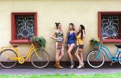 Les filles chics de boho heureux posent avec des bicyclettes près de la façade de maison photographie stock