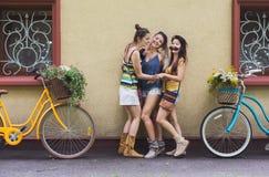 Les filles chics de boho heureux posent avec des bicyclettes près de la façade de maison Image stock