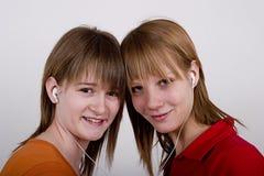 Les filles d'années de l'adolescence écoutent la musique MP3 Image stock