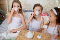 Les filles d'enfant se réveillent dans son lit dans le matin de Noël Images stock