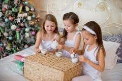 Les filles d'enfant se réveillent dans son lit dans le matin de Noël Photos libres de droits