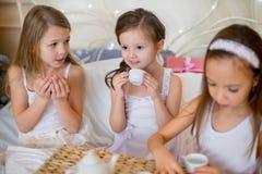 Les filles d'enfant se réveillent dans son lit dans le matin de Noël Image stock