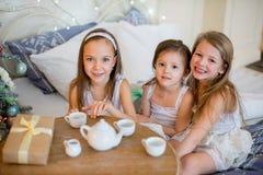 Les filles d'enfant se réveillent dans son lit dans le matin de Noël Image libre de droits