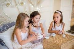 Les filles d'enfant se réveillent dans son lit dans le matin de Noël Photo stock