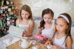 Les filles d'enfant se réveillent dans son lit dans le matin de Noël Photo libre de droits