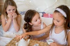Les filles d'enfant se réveillent dans son lit dans le matin de Noël Photographie stock libre de droits