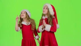 Les filles d'enfants dans les costumes de Noël gonflent le pollen stellaire Écran vert banque de vidéos