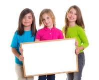 Les filles d'enfants groupent retenir l'espace blanc de copie de panneau blanc Image stock