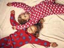Les filles dans des pyjamas dorment dans le lit, vue supérieure Images stock