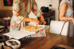 Les filles dans des robes de chambre ont commandé la pizza Image stock