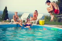 Les filles dans la piscine ont effrayé par leur ami masculin tandis que saut dans la piscine Photographie stock