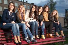 Les filles dans une ville stationnent sur un banc Images libres de droits