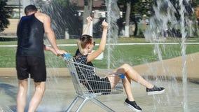 Les filles de garçons ont roulé les chariots - une fontaine pendant l'été banque de vidéos