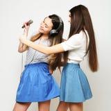 Les filles de hippie de beauté avec un microphone chantant et prennent la photo Photographie stock libre de droits