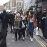Les filles de hippies se sont habillées dans le style frais de Londonien marchant dans la ruelle de brique, une rue populaire par Photo stock