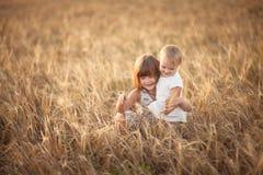 Les filles de soeurs marchent dans le domaine avec le coucher du soleil de seigle Photographie stock