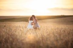 Les filles de soeurs marchent dans le domaine avec le coucher du soleil de seigle Image stock