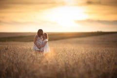 Les filles de soeurs marchent dans le domaine avec le coucher du soleil de seigle Photos libres de droits