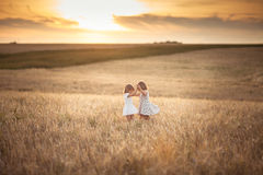 Les filles de soeurs marchent dans le domaine avec le coucher du soleil de seigle Photos stock