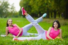 Les filles de sport de forme physique dans les vêtements de sport faisant la forme physique de yoga exercent extérieur Photographie stock