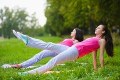 Les filles de sport de forme physique dans les vêtements de sport faisant la forme physique de yoga exercent extérieur Image stock