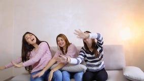Les filles drôles écoutent la musique et la danse, les sourires sur leurs visages et se reposer sur le fond de sofa du mur léger  banque de vidéos