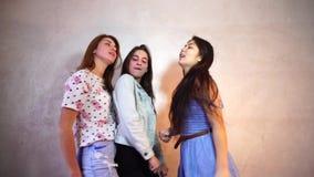 Les filles drôles posent in camera avec des sourires sur leurs visages et se tiennent sur le fond du mur léger dans la chambre clips vidéos