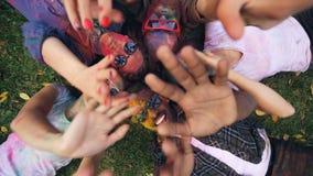 Les filles et les types joyeux se trouvent sur l'herbe en parc, leurs visages et l'habillement sont couverts de peinture multicol banque de vidéos