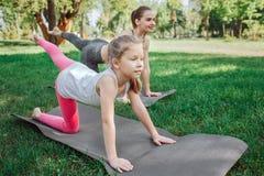 Les filles excercising dehors en parc Ils étirent leurs jambes gauches et se penchent sur des mains et de bonnes jambes Image stock