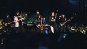 Les filles expressives et émotives de violoniste exécutent sur l'étape avec un groupe de rock banque de vidéos