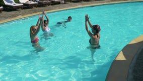Les filles faisant la forme physique s'exerce dans la piscine et le type passe par et cesse de regarder clips vidéos