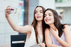 Les filles font un repos en café et font des selfies Images stock
