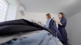 Les filles fouillent dans leurs propres choses Démontez les vêtements dans des catégories banque de vidéos