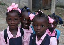 Les filles haïtiennes d'école catholique posent pour l'appareil-photo sur le chemin à l'école dans le village rural Photo stock