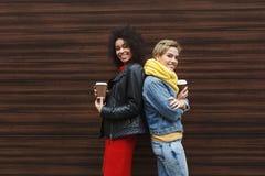 Les filles heureuses avec emportent le café dehors Photographie stock libre de droits