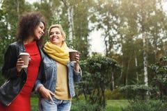 Les filles heureuses avec emportent le café dehors Photo stock