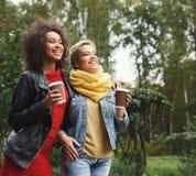 Les filles heureuses avec emportent le café dehors Images stock