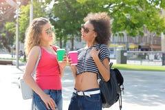 Les filles heureuses avec emportent le café dehors Image stock
