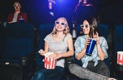 Les filles heureuses et belles s'asseyent dans le hall de cinéma et le film de observation La fille blonde semble droite et souri Photographie stock