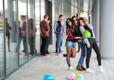 Les filles heureuses et les garçons de l'adolescence ayant le bon amusement chronomètrent dehors Images libres de droits