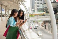 Les filles heureuses passent en revue l'emplacement de magasin par le smartphone Photo stock