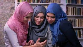 Les filles impressionnantes portant le hijab regardent le téléphone et sourient tout en se tenant ensemble dans la bibliothèque,  clips vidéos