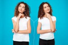 Les filles jumelle la musique de écoute dans des écouteurs, pensant au-dessus du fond bleu Photos stock