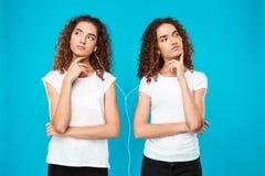 Les filles jumelle la musique de écoute dans des écouteurs, pensant au-dessus du fond bleu Image stock