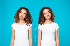 Les filles jumelle la musique de écoute dans des écouteurs, souriant au-dessus du fond bleu Photographie stock