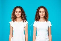 Les filles jumelle la musique de écoute dans des écouteurs, souriant au-dessus du fond bleu Images stock