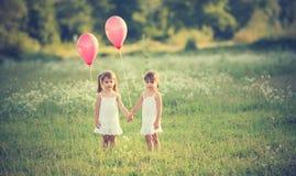 Les filles jumellent des soeurs avec des ballons pendant l'été Photos stock
