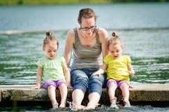 Les filles jumelles de mère et de petits enfants jouent sur un lac Photos stock