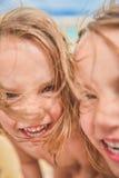 Les filles jumelles regardent l'appareil-photo et rire Images stock