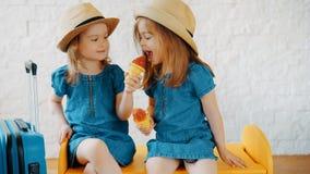 Les filles mangent la crème glacée à la maison tout en attendant des vacances Photographie stock